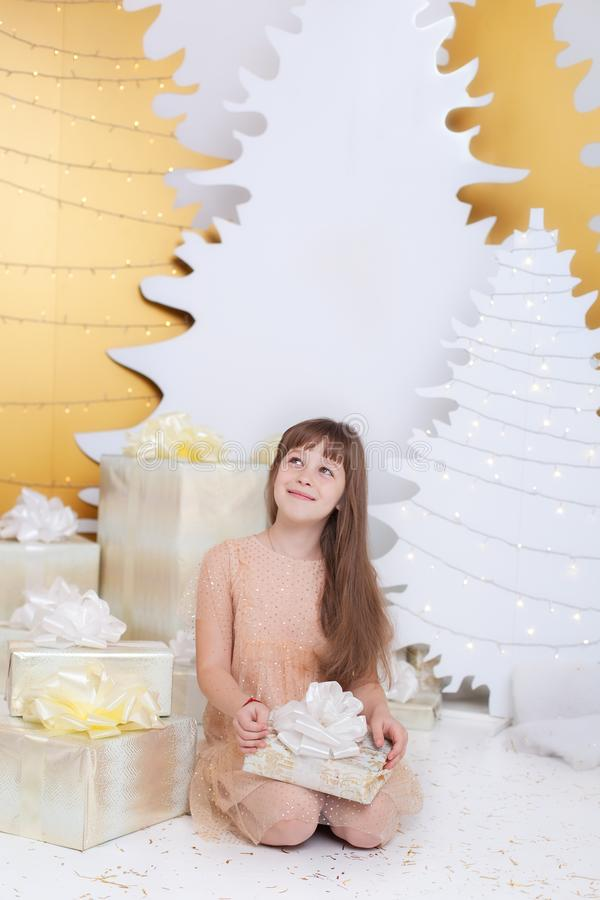 Young girl in golden dress laughs and enjoys gift. Little girl opening magical christmas present at home. child holds christmas pr stock photo