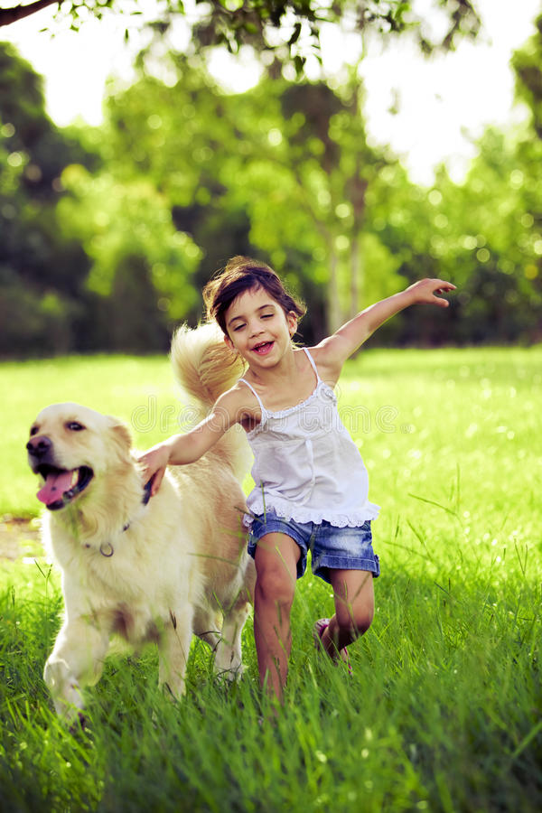 Young girl with golden retriever running royalty free stock photo