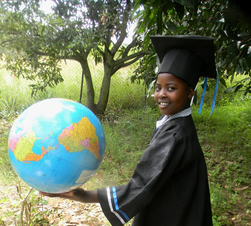 Young girl in graduation attire holding world globe-map in h. Young girl in graduation gown and cap holding world globe map in hand whilst standind outdoors with royalty free stock images