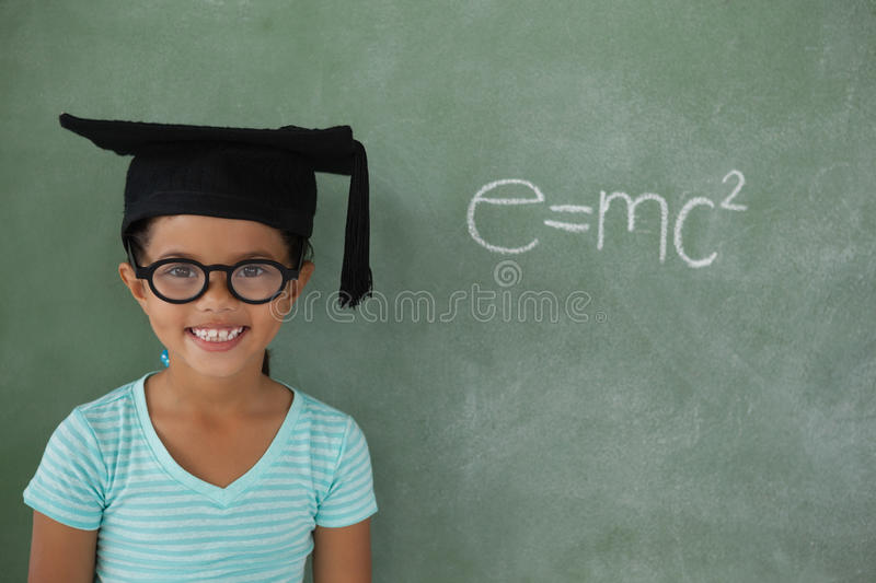Young girl with graduation hat against chalk board. Portrait of young girl with graduation hat against chalk board stock photo