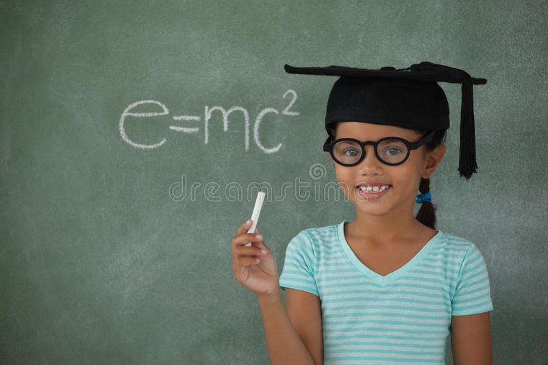 Young girl with graduation hat holding chalk. Against chalk board royalty free stock image