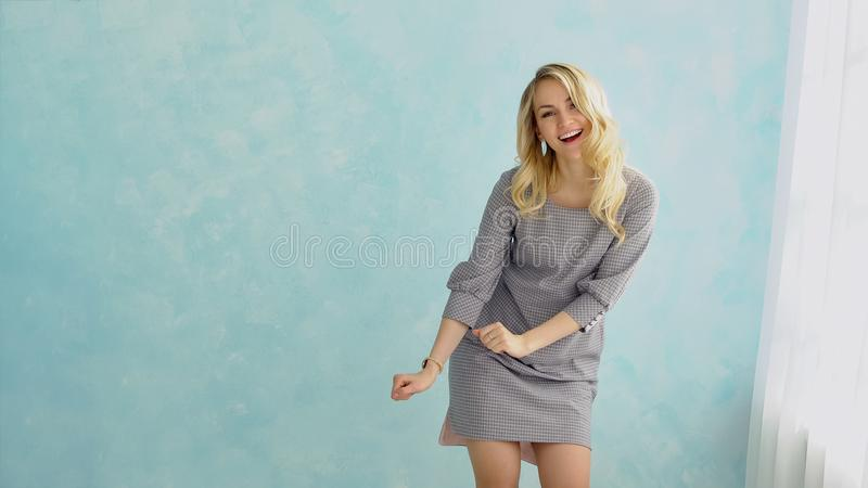 Young girl in gray dress is dancing against a blue wall next to the window. royalty free stock photos