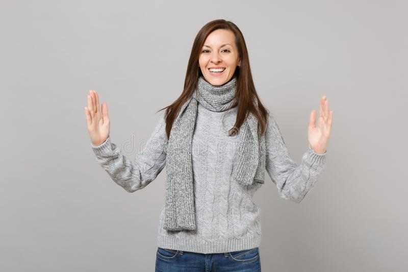 Young girl in gray sweater scarf gesturing demonstrating size with horizontal workspace on grey background. Healthy fashion lifestyle people emotions cold stock image
