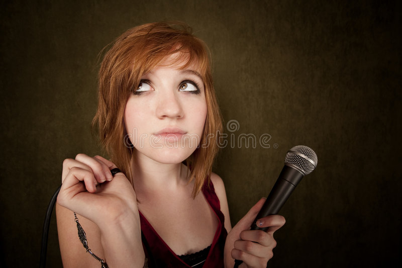 Young girl on a green background with microphone. Pretty young girl with red hair on a green background with microphone stock photos