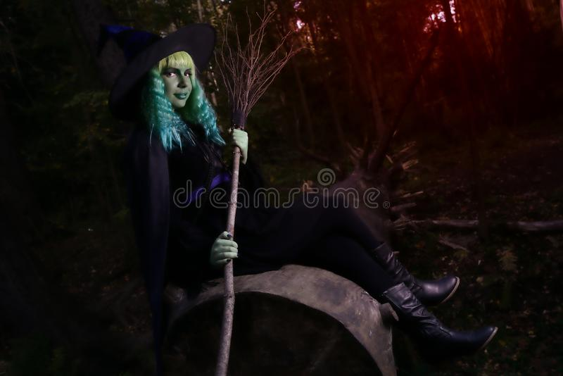 download young girl with green hair and broom in suit of witch in forest halloween