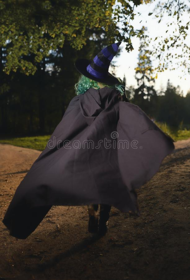 Young girl with green hair and skin suit of witch in forest. Halloween time royalty free stock photography