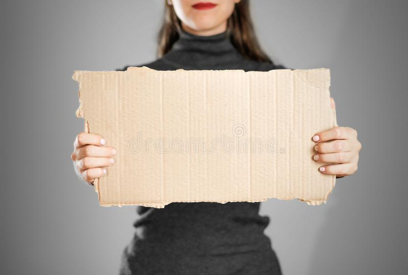 A young girl in a grey jacket holding a piece of cardboard. Prep royalty free stock photos