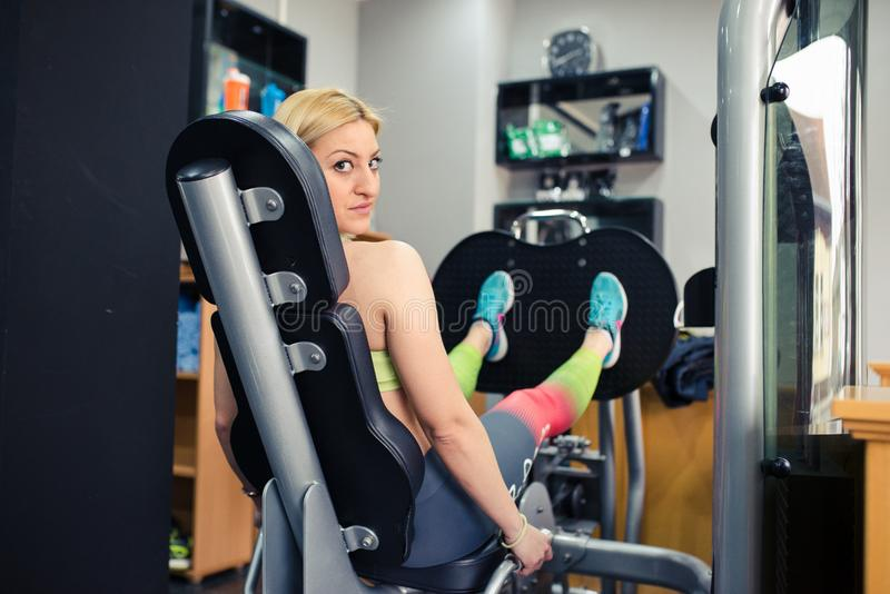 Young girl in gym, exercising her legs. On leg press royalty free stock image