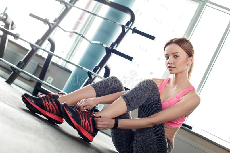 Young girl in gym healthy lifestyle sitting tying shoelaces looking camera sensual stock image