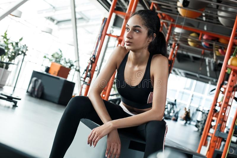 Young woman in gym sporty lifestyle sitting looking out the window dreaming royalty free stock image