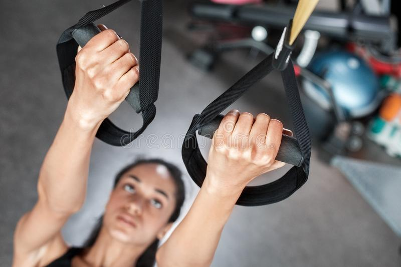 Young woman in gym sporty lifestyle total resistance workout hanging on suspansion straps close-up royalty free stock image