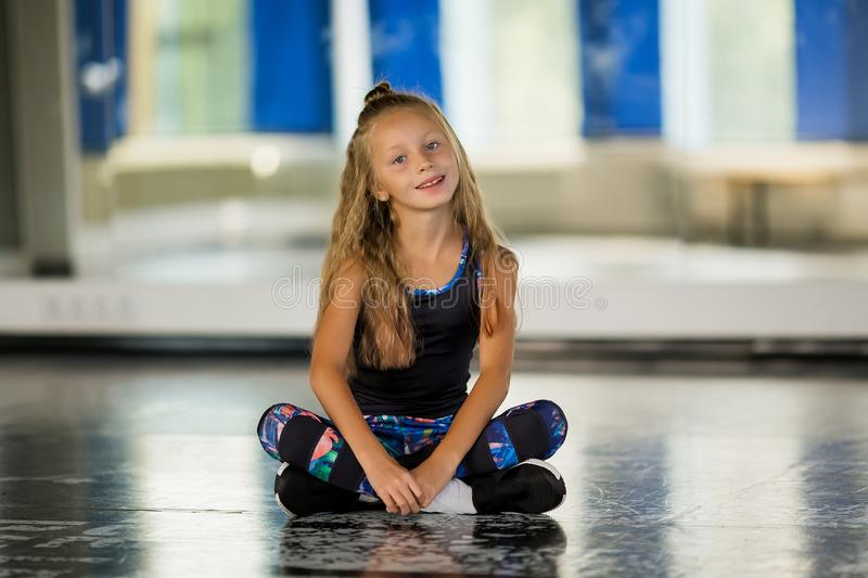 A young girl gymnast in a black leotard looks to the camera. Girl dancing modern choreography. Hip Hop Girl royalty free stock image