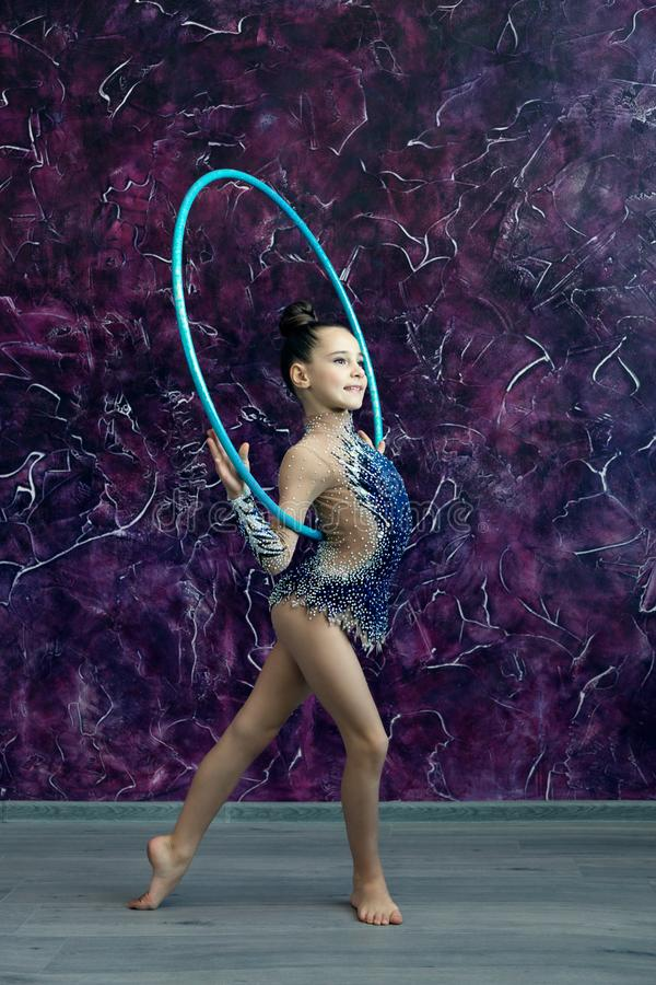 A young girl gymnast in a blue suit with rhinestones is standing on the office of the violet wall, holding a hoop behind her back royalty free stock photos