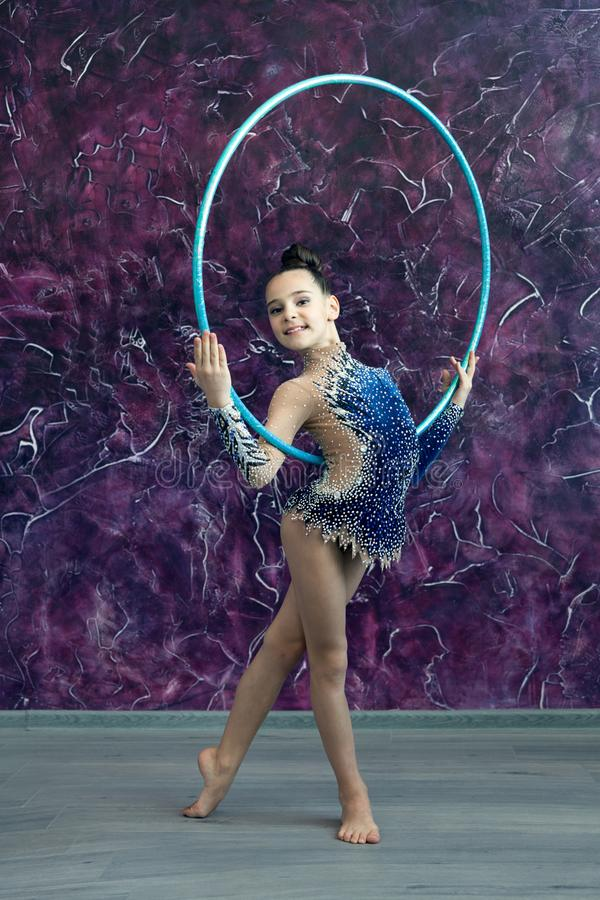 A young girl gymnast in a blue suit with rhinestones is standing on the office of the violet wall, holding a hoop royalty free stock images