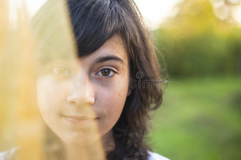 Young girl, half of the face is covered by translucent veil. royalty free stock image