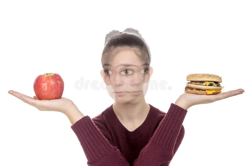 Young Girl with a hamburger and an apple royalty free stock photos