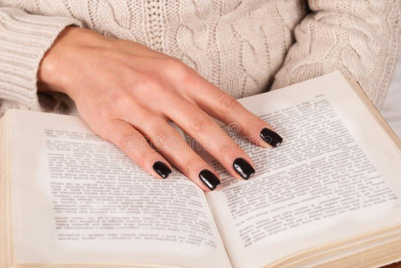 Young Girl hand with black nails holds book, woman in sweater reading book. Young Girl hand with black nails manicure holds book, woman in wool sweater reading royalty free stock photos