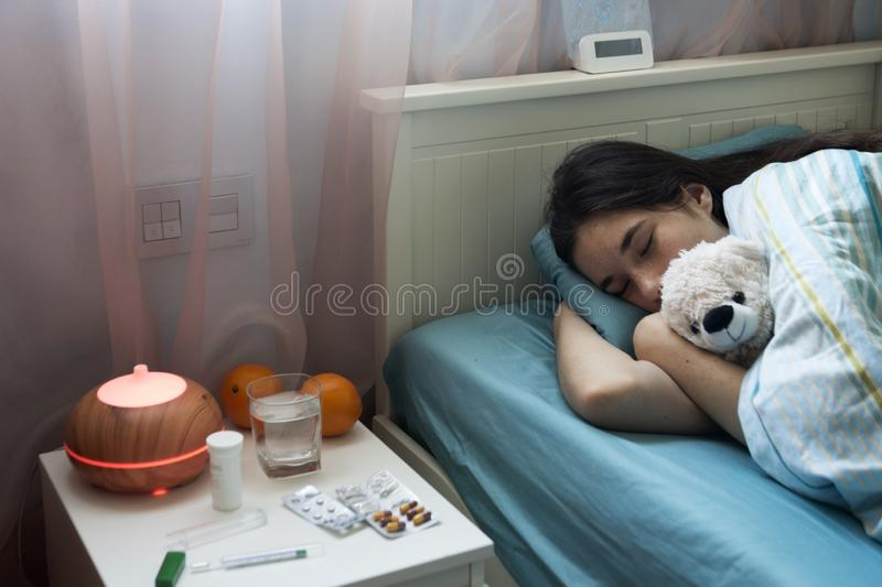 Teenage girl in bed at home caught cold, feeling bad, sleeping. stock photo