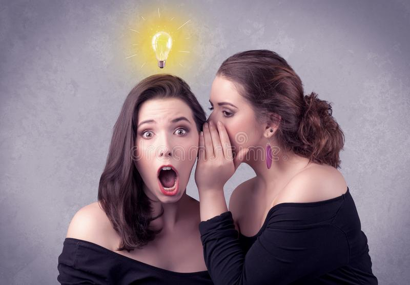 Girl telling secret things to her girlfriend. A young girl has an idea illustrated with a drawn glowing light bulb above the head, while a friend whispers a royalty free stock photo