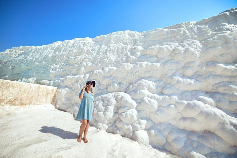 Young girl in hat looking on travertine pools and terraces in Pamukkale. Cotton castle in southwestern Turkey stock photography