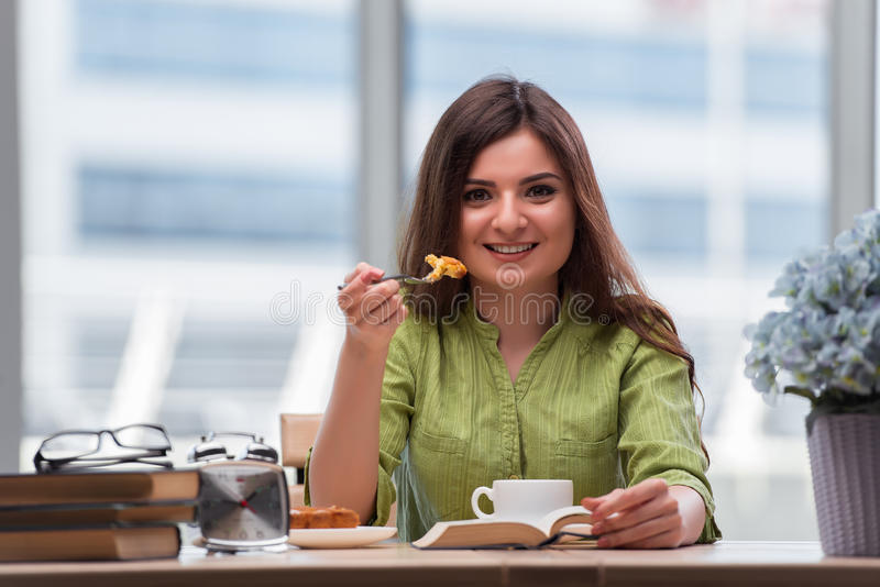 The young girl having breakfast at home royalty free stock images