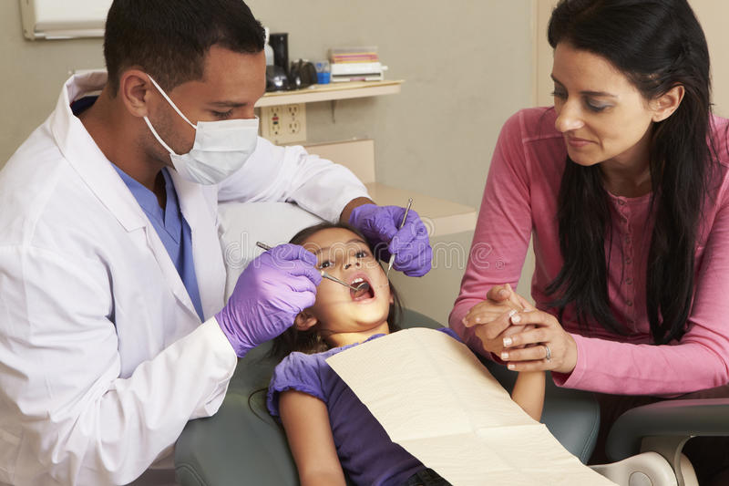Young Girl Having Check Up At Dentists Surgery With Mother royalty free stock photos