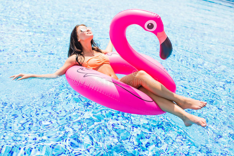 Young girl having fun and laughing and having fun in the pool on an inflatable pink flamingo in a bathing suit and sunglasses in s. Young girl having fun and royalty free stock images