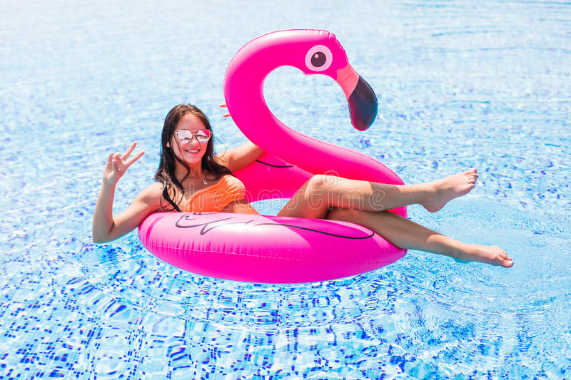 Young girl having fun and laughing on an inflatable giant pink flamingo pool float mattress in a bikini. Attractive tanned woman l. Young and girl having fun and royalty free stock photography