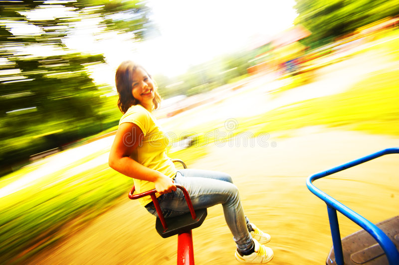 Young girl having fun on roundabout stock photo