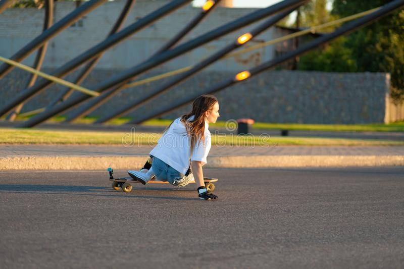 Young girl having fun with skateboard on the road. Young woman skating on a sunny day stock photo