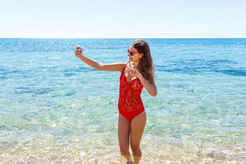 Young girl having fun taking smartphone selfie pictures of herself. travel holidays stock images
