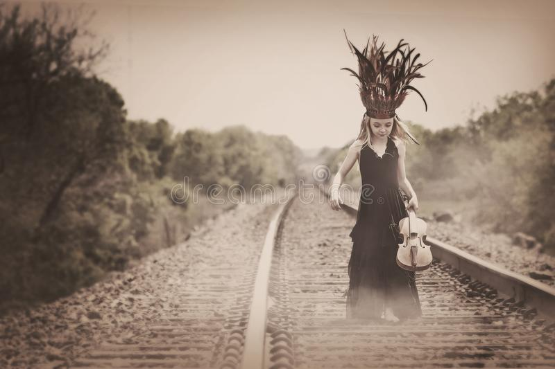 Young girl headdress. Violin Indian railroad tracks vintage royalty free stock images