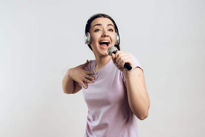 Young girl in headphones expressively sings stock images