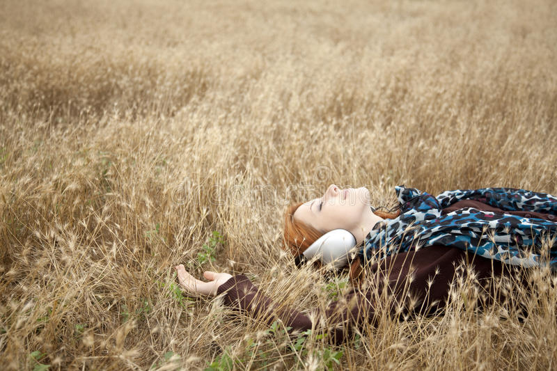 Young girl with headphones lying at field.