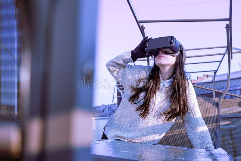 VR pink purple blue girl face woman virtual reality headset brunette phone futuristic violet sky furniture winter. A young girl with a headset on the face meets royalty free stock photography