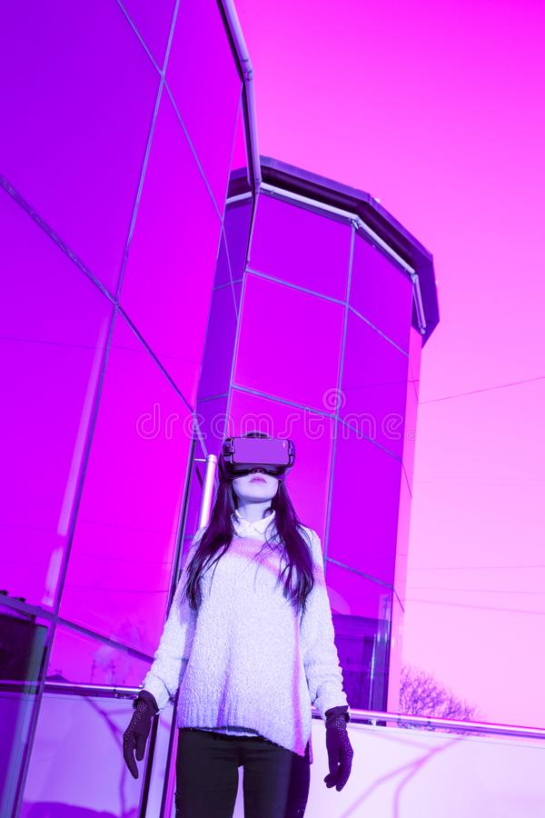 VR pink purple blue girl face woman virtual reality headset brunette phone futuristic violet sky furniture winter. A young girl with a headset on the face meets royalty free stock photos