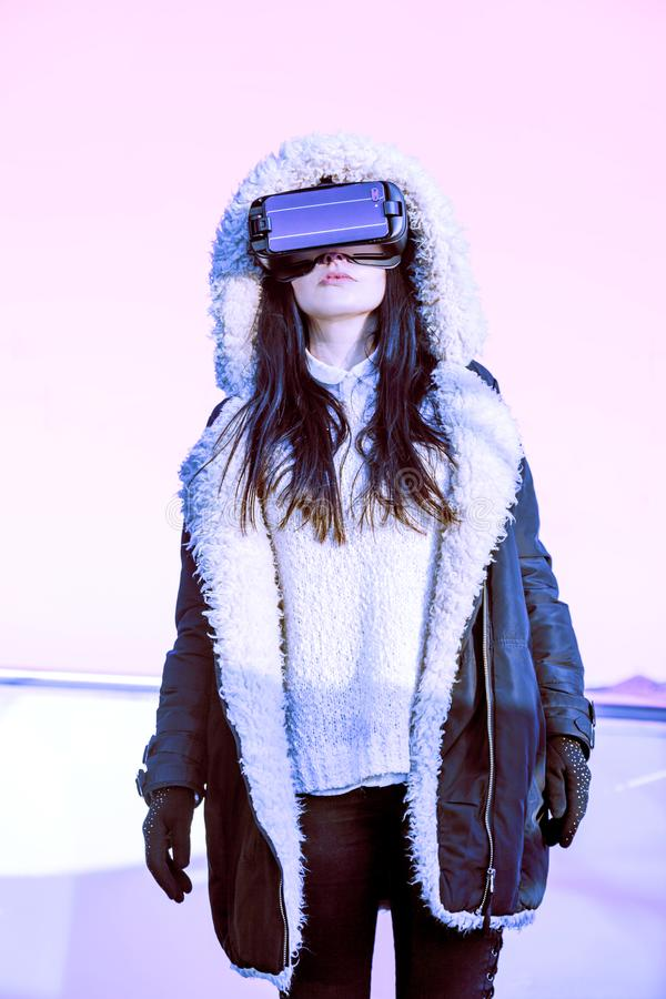 VR pink purple blue girl face woman virtual reality headset brunette phone futuristic violet sky furniture winter. A young girl with a headset on the face meets stock photography