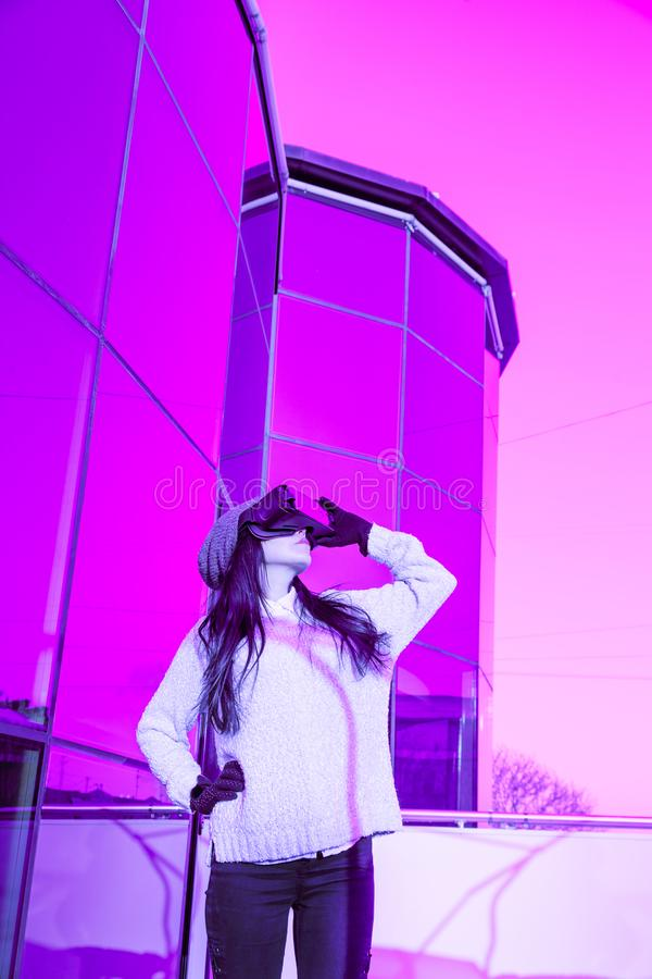 VR pink purple blue girl face woman virtual reality headset brunette phone futuristic violet sky furniture winter. A young girl with a headset on the face meets royalty free stock photo