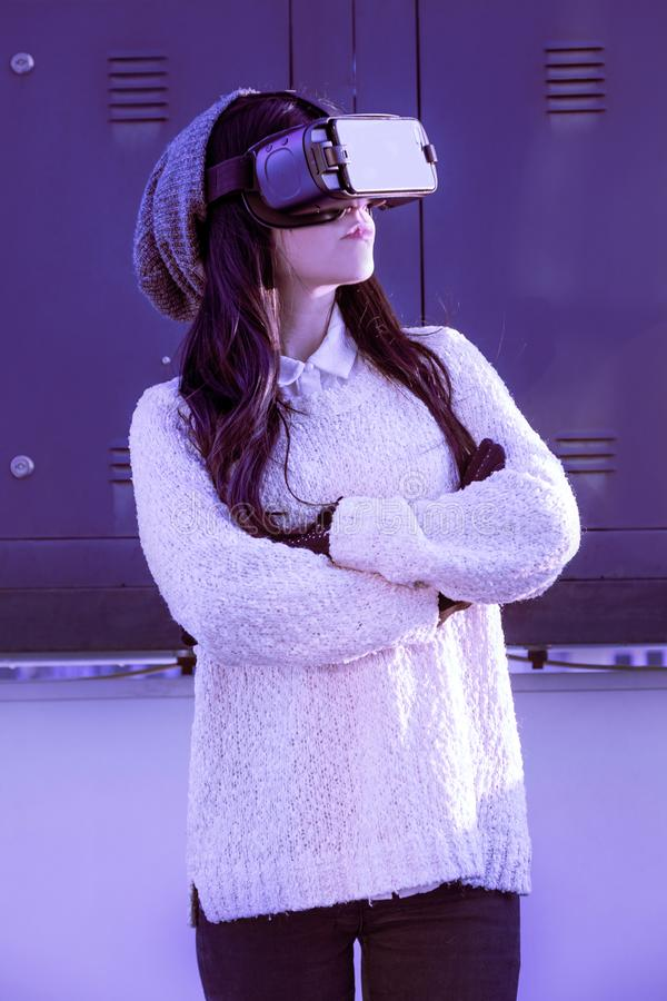 VR pink purple blue girl face woman virtual reality headset brunette phone futuristic violet sky furniture winter. A young girl with a headset on the face meets royalty free stock image