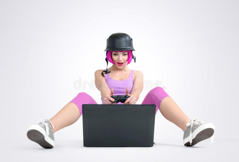Young girl in the helmet with joystick sits on the floor and playing game on a laptop royalty free stock images