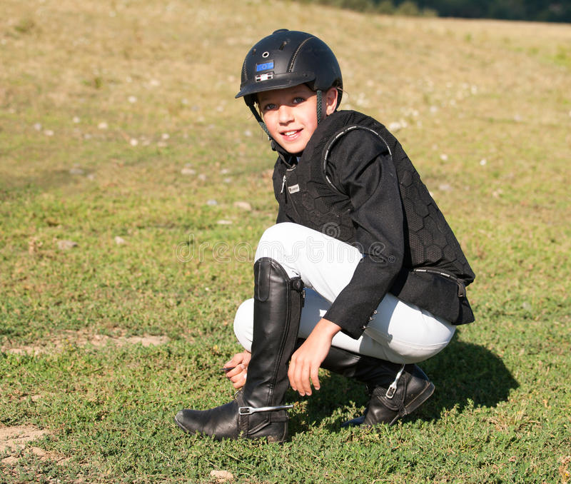 Young girl in helmet preparing spurs before showjumping competition stock image