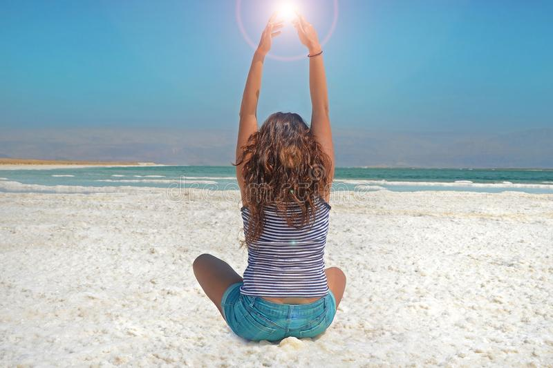 Young girl with her hands is catching the energy of the sun. long-haired girl sits on the shore of the Dead Sea in Israel.  stock photo