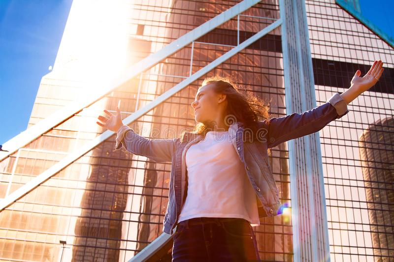 Young girl with her hands wide open with the city in the background. Concept of freedom. The love and emotions, a woman`s happiness. Sunset over the city stock image