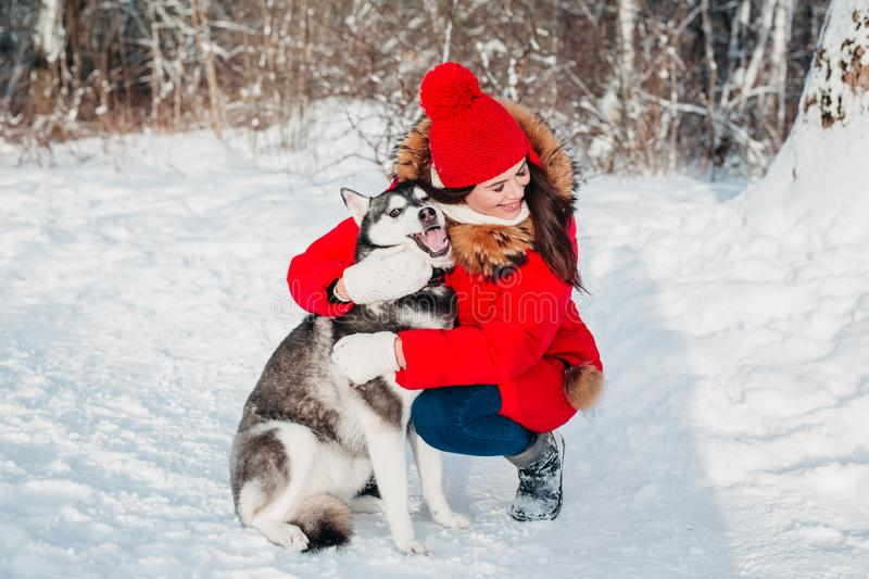 Young girl with her husky dog in winter park. Domestic pet. Husky. Young girl with her husky dog outdoor at winter. Domestic pet. Husky royalty free stock images