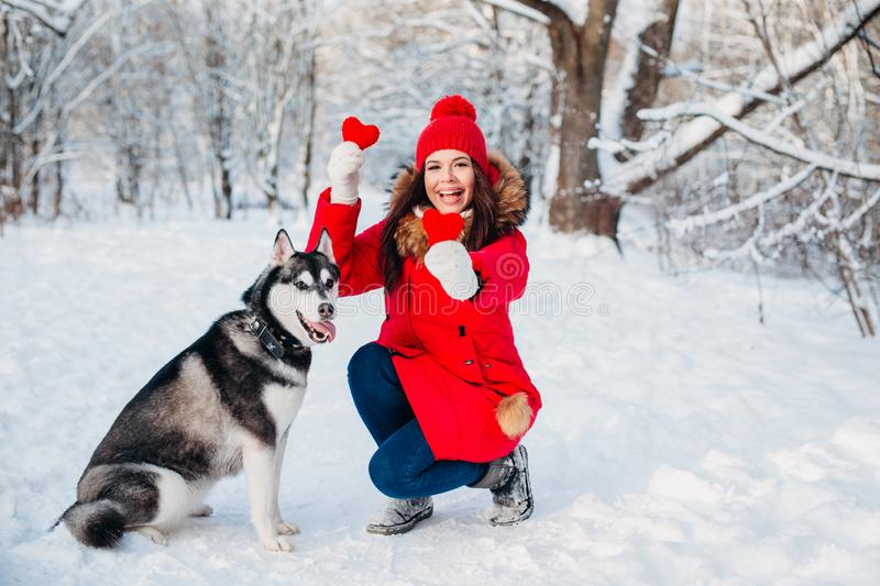 Young girl with her husky dog in winter park. Domestic pet. Husky. Animal love stock photo
