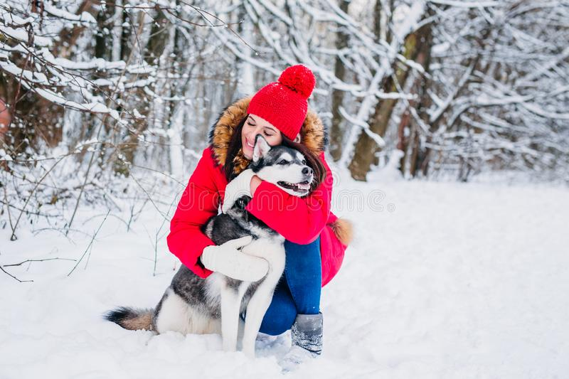 Young girl with her husky dog in winter park. Domestic pet. Husky. Young girl with her husky dog in winter forest. Domestic pet. Husky royalty free stock photography