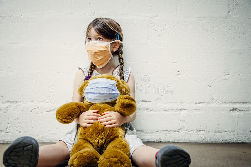 Young girl and her teddy bear wearing protective masks royalty free stock photo
