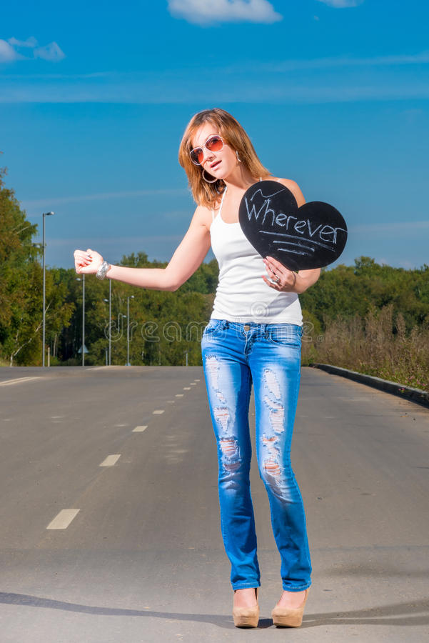 Young girl hitchhiking on a road. Young girl hitchhiking on a country road royalty free stock images