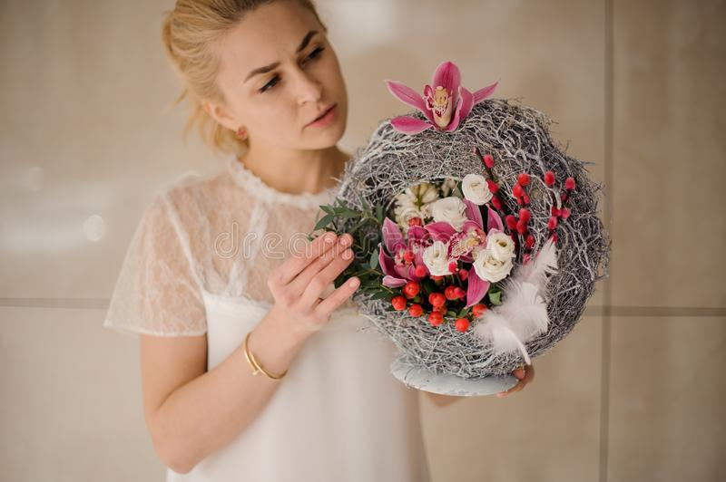 Girl holding a spring composition of different colour flowers, berries and feather stock photography