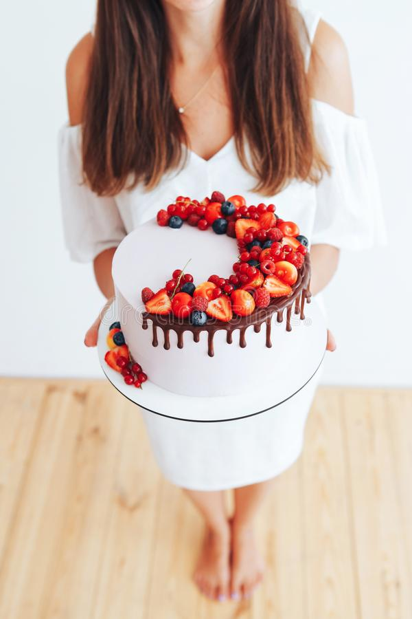 Young girl holding a cake. Cake with white cheese cream, decorated with ganache and red berries on a white stand royalty free stock photography